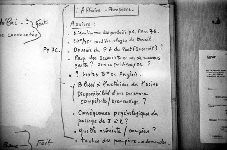 Franck Pourcel | La petite mer des oubliés – Luttes | 1996-2006 | Luttes | Photographie en N/B d'un tableau avec les inscriptions concernant la réduction du personnel chez les pompiers