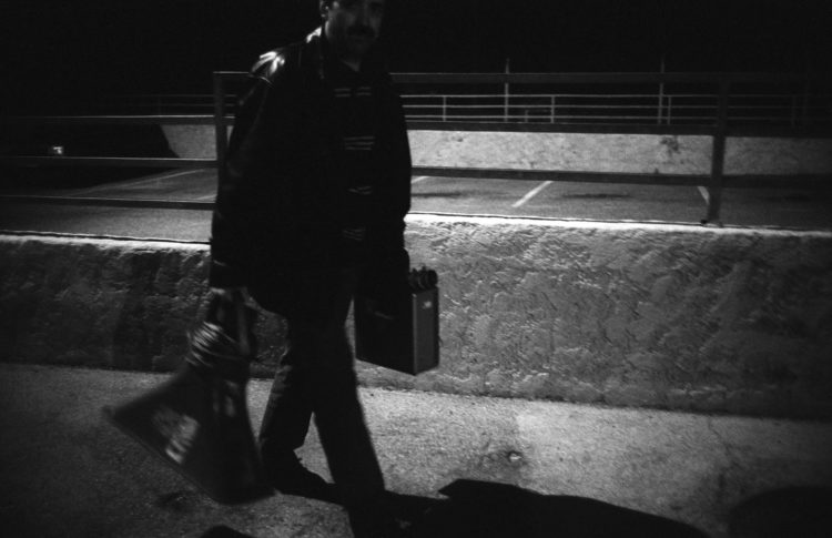 Franck Pourcel | La petite mer des oubliés – Luttes | 1996-2006 | Luttes | Photographie en N/B d'un homme qui porte porte un haut parleur pour une manifestation devant l'usine pétrochimique