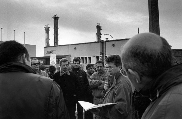 Franck Pourcel | La petite mer des oubliés – Luttes | 1996-2006 | Luttes | Photographie en N/B d'un mouvement de manifestation devant l'usine pétrochimique à Lavéra