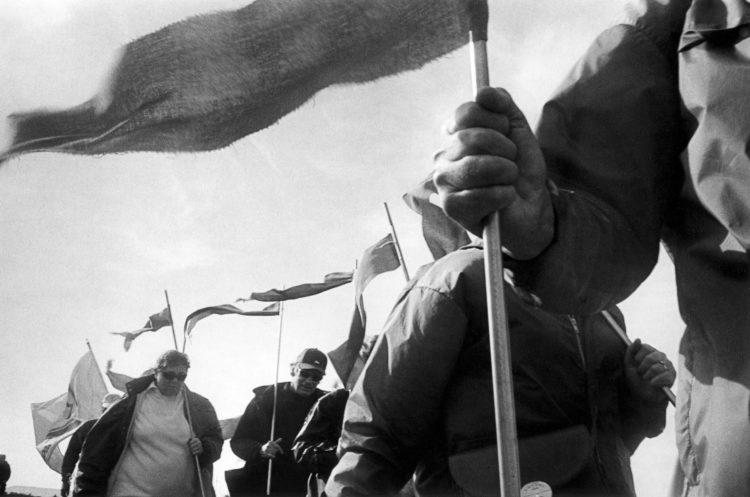 Franck Pourcel | La petite mer des oubliés – Luttes | 1996-2006 | Luttes | Photographie en N/B d'un groupe de manifestant avec des drapeaux (bleus) pour manifester contre l'usine hydro-électrique de St Chamas