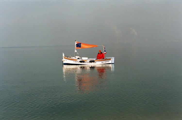 Luttes | Photographie en couleur d'un homme sur une barque pour dénocer la pollution