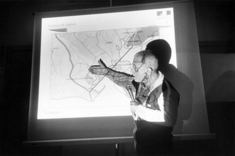 Franck Pourcel | La petite mer des oubliés – Luttes | 1996-2006 | Luttes | Photographie en N/B d'une réunion et prise de parole par un ingénieur sur la déviation du canal de la Durance