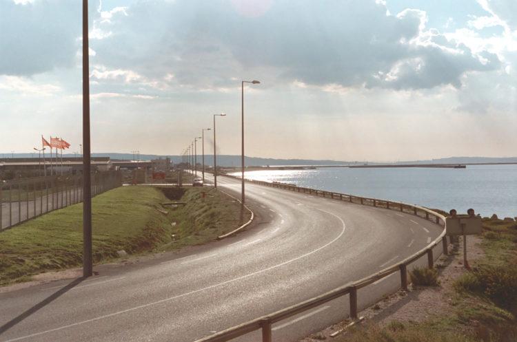 Franck Pourcel | La petite mer des oubliés – Paradoxes | 1996-2006 | Paradoxes | Photographie en couleur d'une route entre l'étang et les entreprises de l'aéroport