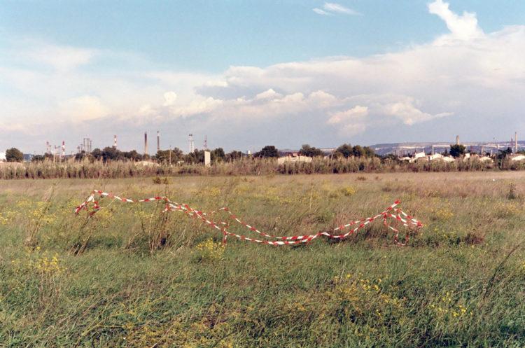 Franck Pourcel | La petite mer des oubliés – Paradoxes | 1996-2006 | Paradoxes | Photographie en couleur d'une bande barrière rouge et blanc au milieu d'un champ
