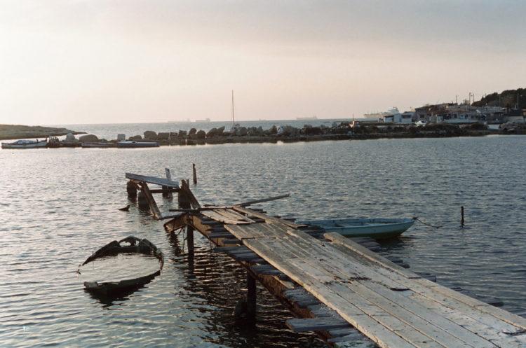 Franck Pourcel | La petite mer des oubliés – Paradoxes | 1996-2006 | Paradoxes | Photographie en couleur de la calanque de ponteau avec les cabanons et les pétroliers