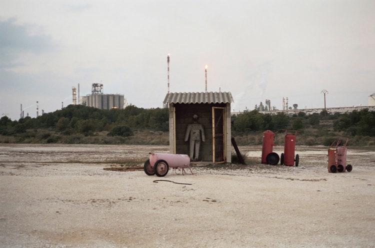 Franck Pourcel | La petite mer des oubliés – Paradoxes | 1996-2006 | Paradoxes | Photographie en couleur du site d'entrainement des pompiers avec matériel de pompier sur un terrain vide avec l'usine pétrochimique en fond