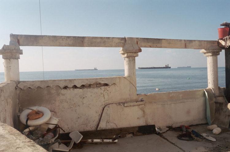 Franck Pourcel | La petite mer des oubliés – Paradoxes | 1996-2006 | Paradoxes | Photographie en couleur d'une terrasse donnant sur la mer avec des pétroliers en vue