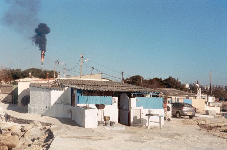 Franck Pourcel | La petite mer des oubliés – Paradoxes | 1996-2006 | Photographie en couleur d'un village de cabanon avec une grosse fumée noire qui sort d'une torchère de l'usine pétrochimique de Lavéra