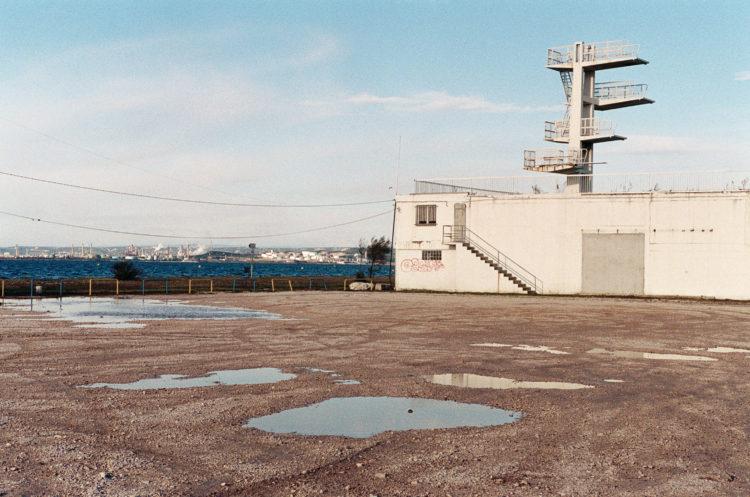 Franck Pourcel | La petite mer des oubliés – Paradoxes | 1996-2006 | Paradoxes | Photographie en couleur d'une piscine avec un plongeoir devant l'étang avec l'usine pétrochimique en fond