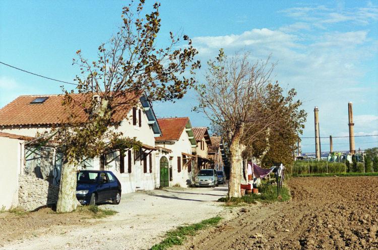 Franck Pourcel | La petite mer des oubliés – Paradoxes | 1996-2006 | Paradoxes | Photographie en couleur d'un quartier de ville avec maisons et champs devant usine pétrochimique