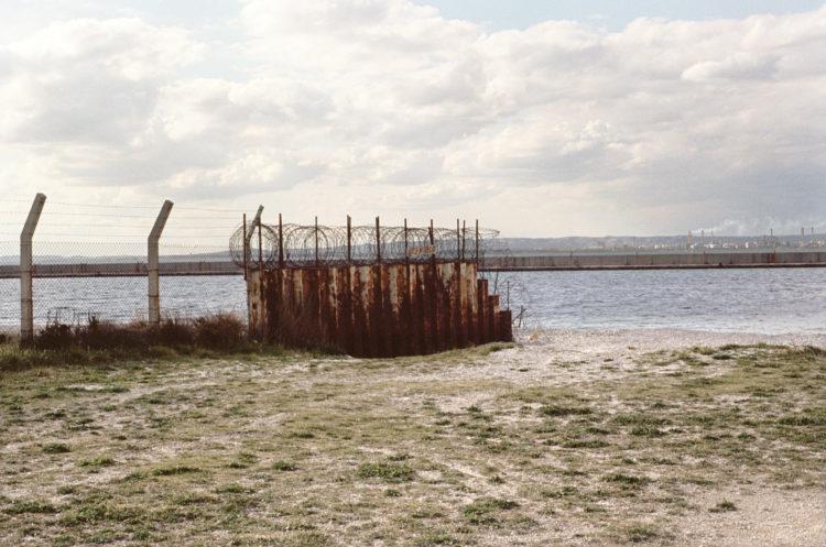 Franck Pourcel | La petite mer des oubliés – Paradoxes | 1996-2006 | Paradoxes | Photographie en couleur d'un grillage barrant l'entée sur l'aéroport devant l'étang, l'usine pétrochimique en fond