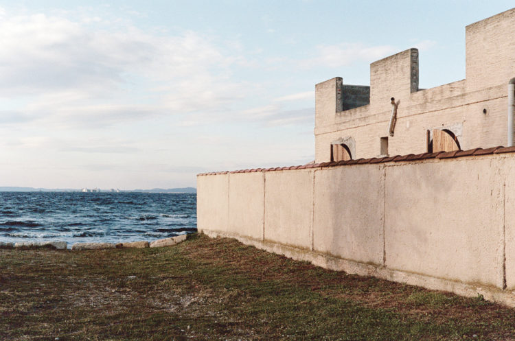 Franck Pourcel | La petite mer des oubliés – Paradoxes | 1996-2006 | Paradoxes | Photographie en couleur d'une maison avec des crénaux devant l'étang