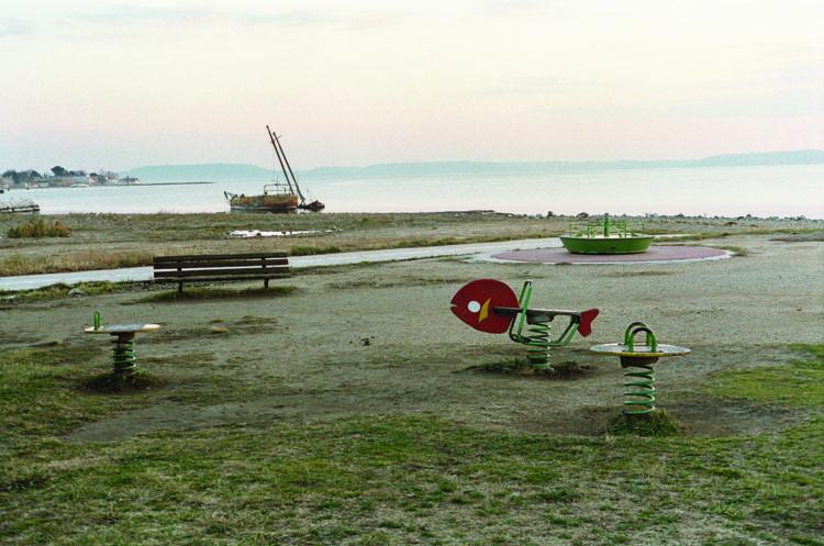 Franck Pourcel | La petite mer des oubliés – Paradoxes | 1996-2006 | Paradoxes | Photographie en couleur d'une place pour enfants devant l'étang avec bateau échoué