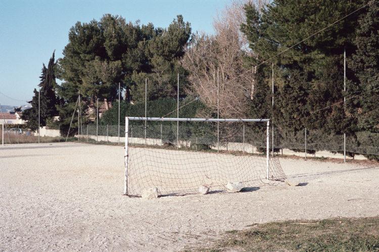 Franck Pourcel | La petite mer des oubliés – Paradoxes | 1996-2006 | Paradoxes | Photographie couleur d'un stade de foot en sabilisé, de grosses pierres tiennent les filets des buts