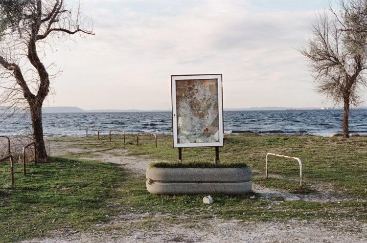 Franck Pourcel | La petite mer des oubliés – Paradoxes | 1996-2006 | Paradoxes | Photographie en couleur d'un porte affiche d'informations avec des impacts sur la vitre