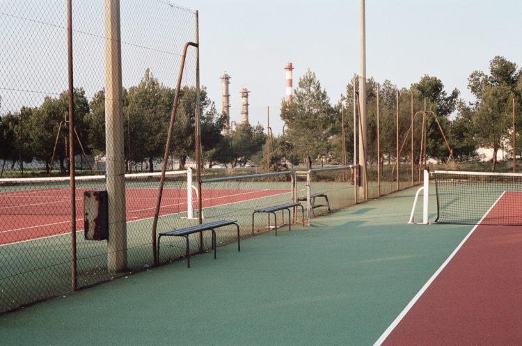 Franck Pourcel | La petite mer des oubliés – Paradoxes | 1996-2006 | Paradoxes | Photographie en couleur d'un terrain de tennis dans un quartier résidentiel sur fond d'usine pétrochimique