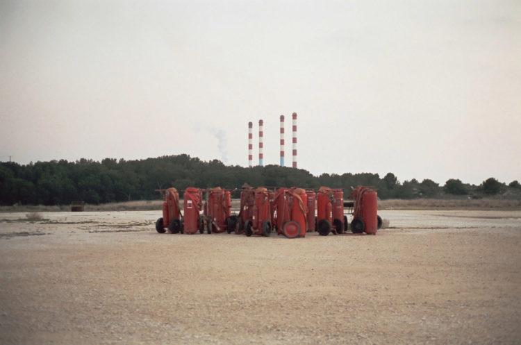 Franck Pourcel | La petite mer des oubliés – Paradoxes | 1996-2006 | Paradoxes | Photographie en couleur du site d'entrainement des pompiers avec matériel de pompier sur un terrain vide avec l'usine électrique de Ponteau en fond
