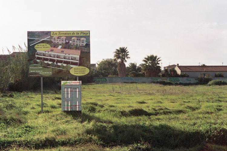 Franck Pourcel | La petite mer des oubliés – Paradoxes | 1996-2006 | Paradoxes | Photographie en couleur d'un terrain proche de la plage du Jaï avec un panneau d'une future construction sur un terrain vide